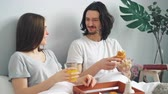 kruvasan : Happy young people are laughing chatting eating breakfast in bed at home enjoying croissants and orange juice. Youth lifestyle, relationship and food concept.