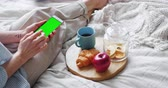 онлайн : Female hand is using green screen mock up smartphone in bed during breakfast at home swiping touching device. People, modern technology and social media concept.