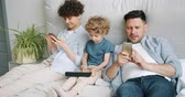 онлайн : Man and woman are using smartphones checking social media while little kid is playing game on tablet in bed at home. Internet addiction and family concept. Стоковые видеозаписи