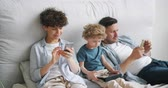 онлайн : Little boy son is playing game on tablet touching screen while parents are using smartphones in bed at home. Modern lifestyle, family and device addiction concept.
