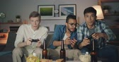 bacharel : Portrait of happy young men playing video game at home at night sitting on sofa together in dark room looking at camera. Entertainment and friendship concept.