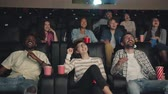 Slow motion of happy millennials girls and guys laughing in dark cinema watching interesting funny film together. Friendship, fun and entertainment concept.