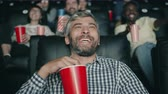 Gray-haired man is laughing at funny comedy in cinema and eating popcorn sitting in chair enjoying movie. Entertainment, snacks and modern lifestyle concept.