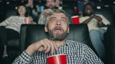 freude : Happy middle-aged man with grey hair is laughing eating tasty popcorn watching movie in cinema having fun. Joyful people, lifestyle and snacks concept.