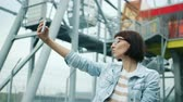 individualidade : Portrait of happy young woman taking selfie with smartphone camera showing hand gestures v-sign and thumbs-up posing enjoying life outside on urban background.