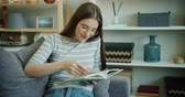 letteratura : Slow motion of pretty young lady smiling reading book resting on sofa at home. Intelligent millennials, modern lifestyle and leisure time in house concept.