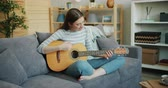 kultur : Beautiful young woman in glasses is playing the guitar sitting on sofa at home in lotus pose enjoying music and free time in apartment. People and skills concept.