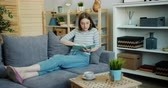 čtenář : Attractive young woman with blond hair is reading interesting book enjoying modern literature sitting on sofa at home alone. Hobby, youth and interior concept.