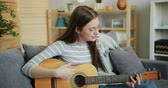 kultur : Attractive young lady in glasses is playing the guitar at home enjoying music and leisure time having fun with musical instrument. Youth and culture concept.
