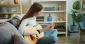 kultur : Slow motion of attractive girl enjoying music playing guitar in apartment sitting on couch alone. Modern lifestyle, musical instruments and youth concept.