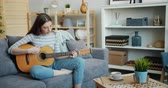 kultur : Pretty young woman is playing the guitar in cozy apartment having fun alone sitting on sofa practising skills. Modern lifestyle, millennials and people concept.