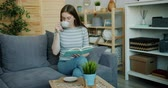 kultur : Cute young woman is reading interesting book and drinking tea indoors in cozy house relaxing on sofa alone enjoying leisure time. Happiness and hobby concept.