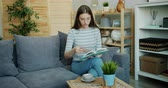 kultur : Smart young lady in glasses is reading interesting book sitting on comfortable sofa in light flat enjoying literature. Happy people and indoor activity concept.