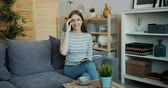kultur : Slow motion portrait of happy young woman holding book at home looking at camera sitting on sofa touching glasses. Youth culture, lifestyle and hobby concept. Stock Footage