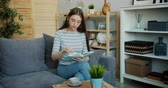 kultur : Portrait of serious young lady is reading modern book sitting on sofa in apartment focused on activity. Light cozy living room is visible in background. Stock Footage