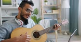 lehre : Slow motion of handsome Arabian musician playing the guitar in front of laptop sitting at table at home alone. Music, entertainment and computers concept. Stock Footage