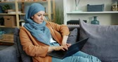портативный : Slow motion of beautiful Middle Eastern woman in hijab using laptop typing working sitting on couch at home. Technology, occupation and people concept.