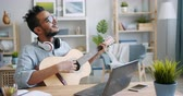 lehre : Bearded African American guy in glasses is playing the guitar and using laptop indoors at home sitting at table alone. People, musical instruments and leisure concept.