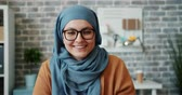 indépendance : Slow motion of pretty girl in hijab and glasses smiling looking at camera in office alone. Modern young people, creative workplace and business ladies concept.