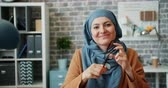 vestuário : Portrait of attractive young Muslim businesswoman in hijab holding glasses sitting in office alone looking at camera with happy face. People and business concept. Vídeos