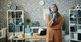 vestuário : Female Muslim office worker in hijab standing in workplace holding glasses looking at camera with serious face. Attractive people, lifestyle and work concept.