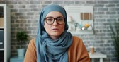 vestuário : Portrait of independent young Muslim girl in hijab and glasses looking at camera in office with serious face. Modern lifestyle, workplace and people concept.
