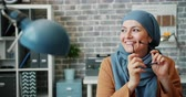 vestuário : Happy mixed race girl in hijab smiling holding glasses in modern office sitting at desk alone enjoying work break. People, lifestyle and workplace concept. Vídeos