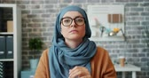 indépendance : Beautiful Muslim girl in hijab is putting on trendy glasses and looking at camera with serious face in office. Business style, people and accessories concept. Vidéos Libres De Droits