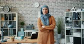 vestuário : Portrait of ambitious mixed race woman in hijab standing in office with arms crossed and looking at camera with serious face. People and modern lifestyle concept.