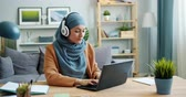 hırslı : Muslim girl freelancer is working with laptop and listening to music in headphones sitting at desk at home. Modern devices, lifestyle and small business concept.