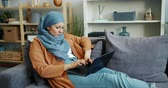 портативный : Independent Muslim girl in hijab is working with laptop in apartment typing busy with work concentrated on project. People, lifestyle and remote job concept. Стоковые видеозаписи