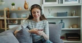 kultur : Beautiful young woman is listening to music with headphones using smartphone smiling relaxing on couch in apartment. Millennials, house and youth culture concept. Stock Footage