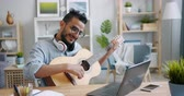kultur : Young bearded Arab in glasses is playing the guitar and using laptop at table in light apartment. Modern technology, music and creative people concept.