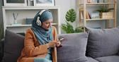 kultur : Cheerful Muslim girl in hijab is using smartphone and listening to music in modern headphones sitting on couch in apartment. Lifestyle and youth concept.