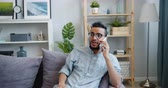 chatten : Handsome Arabian man student is chatting on mobile phone laughing sitting on sofa at home alone. Communication, joyful young people and emotions concept. Stock Footage