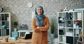 野心的な : Slow motion portrait of successful Muslim businesswoman smiling in office standing alone with arms crossed looking at camera. People, work and success concept.