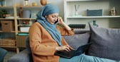портативный : Slow motion of young Muslim businesswoman talking on mobile phone and using laptop sitting on couch at home. Communication, people and devices concept.