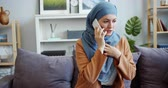 probleme : Stressed Muslim woman in hijab is talking on mobile phone with worried face sitting on couch at home discussing problems. People, communication and emotions concept.