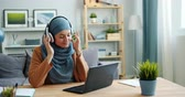 kultur : Modern Muslim lady is enjoying music in headphones working with laptop at home sitting at desk relaxing. People, lifestyle and modern gadgets concept. Stock Footage