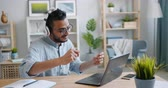 свобода : Slow motion of African American man using laptop and listening to music in headphones at home relaxing and working at table. People and leisure concept.