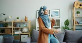 kultur : Slow motion of happy mixed race girl in hijab dancing in headphones at home holding smartphone having fun alone in apartment. Modern lifestyle and people concept.