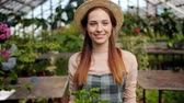 vestuário : Slow motion of joyful female farmer wearing hat and apron walking in glasshouse with box of greenery smiling looking around at flowers. Youth and farming concept.