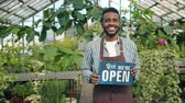 florystyka : Business owner African American man is holding open sign standing in greenhouse smiling looking at camera welcoming people. Floristry and shopping concept. Wideo