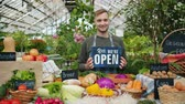 питание : Salesman in apron holding open sign in organic food market welcoming people customers standing near table with vegetables food abd bread smiling looking at camera.