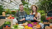 питание : Man and woman in aprons are holding open sign standing at table with organic food in greenhouse market smiling looking at camera welcoming customers.