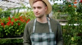питание : Tilt-up shot of man in apron young handsome farmer carrying wooden box of organic vegetables walking in greenhouse alone. Harvest and farmland concept. Стоковые видеозаписи