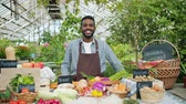 witaminy : Portrait of handsome African American guy farmer standing in farm market smiling looking at camera waiting for customers. People, greenhouse and business concept.