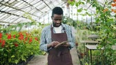note : Slow motion portrait of handsome African American man writing in notepad looking around standing in hothouse alone. Modern farm, people and business concept.