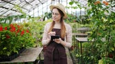 vestuário : Portrait of pretty lady in apron and hat using tablet in greenhouse touching screen counting plants smiling working alone. Modern technology and agriculture concept. Vídeos