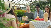 купить : Group of customers is choosing organic food in greenhouse market talking to sales woman pointing at vegetables and fruit. People, business and shopping conceept.